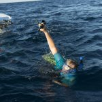SSSG technician Allison Heater swims back to Atlantis' small boat after assisting in Wednesday's launch. She holds a sound-phone used to talk with Alvin's pilot inside the sealed personnel sphere, keeping it above water so it won't get wet.