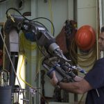 Alvin Expedition Leader Bruce Strickrott isn't arm wrestling with Alvin's portside manipulator arm, but rather placing a sampling device into its gripper.